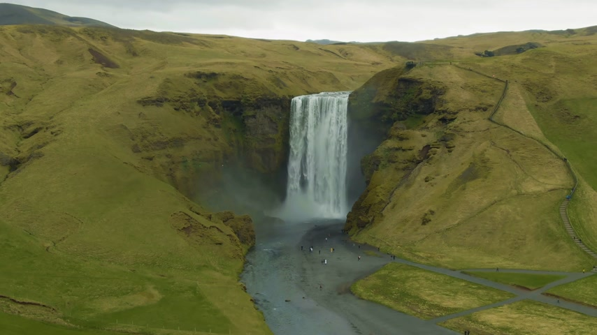 tilt down : Skogafoss Waterfall and Green Landscape at Summer Day. Iceland. Aerial View. Drone is Orbiting Clockwise