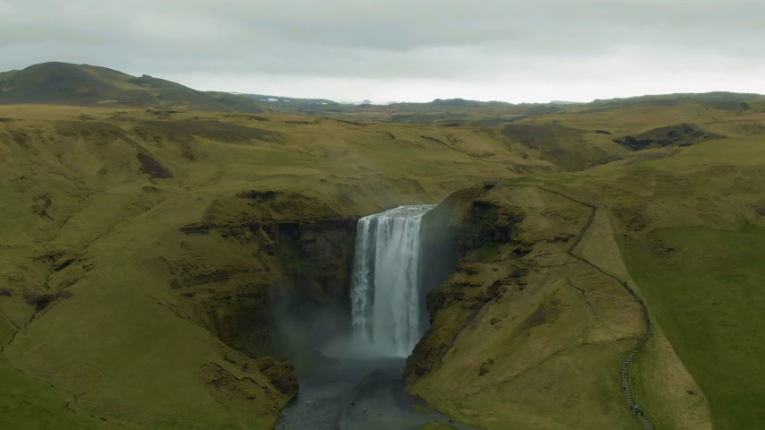 skogafoss : Skogafoss Waterfall and Green Landscape on Cloudy Day. Iceland. Aerial View. Drone Flies Backwards and Upwards