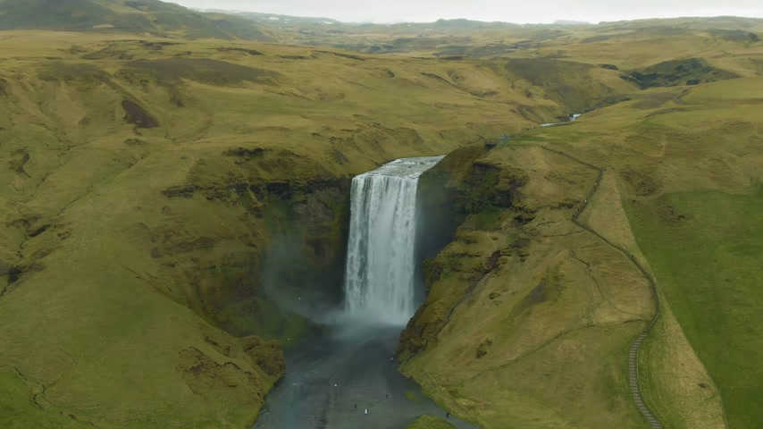 skogafoss : Skogafoss Waterfall and Green Mountains. Iceland. Aerial View. Drone Flies Downwards, Tilt Up