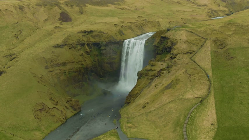 skogafoss : Skogafoss Waterfall and Green Hilly Landscape at Summer Day. Iceland. Aerial View. Drone is Orbiting Stock Footage