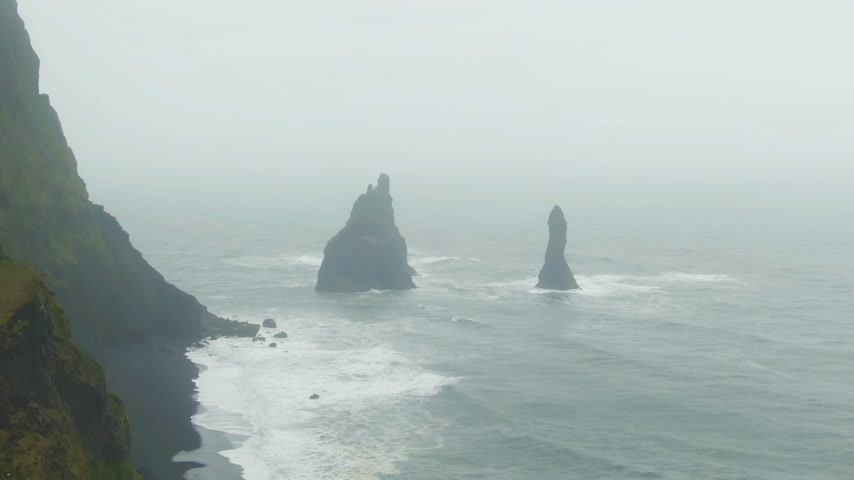 downwards : Reynisdrangar Rocks on Foggy Day. Reynisfjara Beach and Crashing Ocean Waves, Iceland. Aerial View. Drone Flies Downwards, Tilt Up Stock Footage