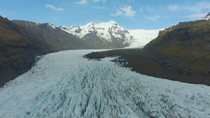 glacier national park : Svinafellsjokull Glacier and Mountain. Vatnajokull. Ash and Crevasses. Iceland. Aerial View. Drone Flies Backwards Stock Footage