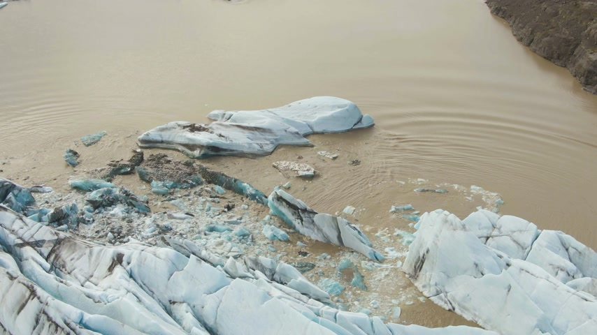 frozen lake : Svinafellsjokull Glacier Calving. Ice Block Falls in Glacial Lake. Iceland. Aerial View. Stock Footage