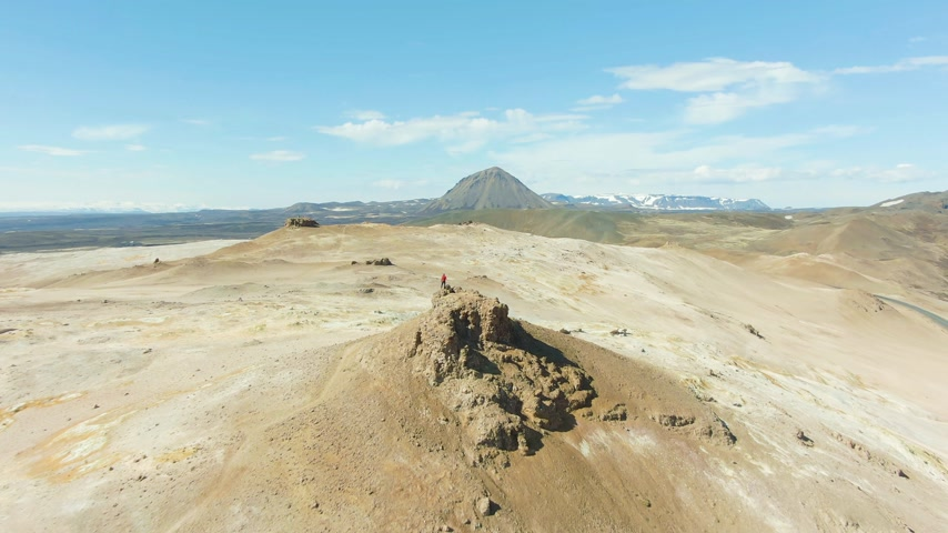 geotermální : Man Stands on Top of Rock in Hverir Geothermal Area. Iceland. Aerial View. Drone Flies Forward