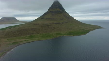 volkanik : Kirkjufell Mountain in Cloudy Summer Day. Iceland. Aerial View. Drone Flies Forward, Tilt Up Stok Video