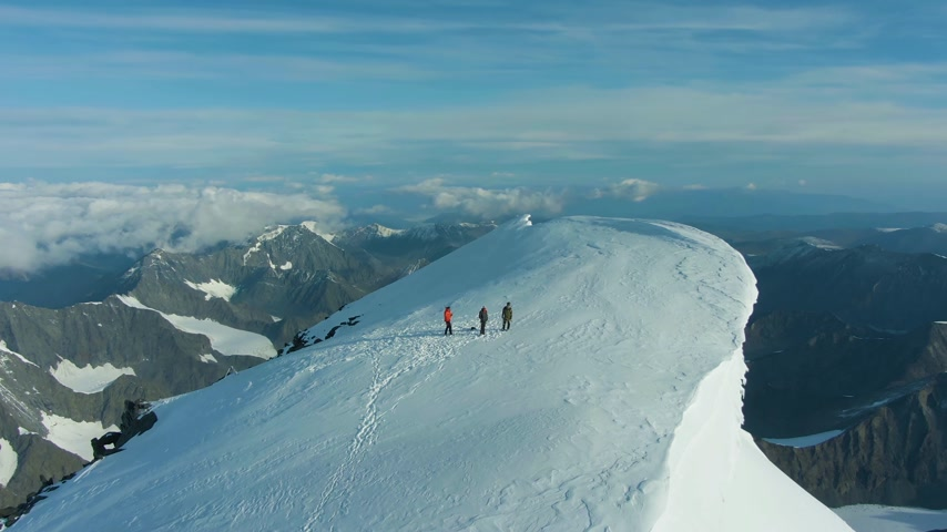 Group of People on Top of Snow-Capped Mountain in European Alps in Sunny Morning. Aerial View. Drone is Orbiting