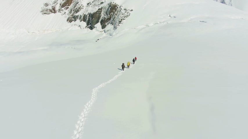 Group of Mountaineers is Roped Together, Walking in Snowy Mountains on Sunny Day. Aerial View