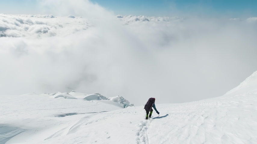 Mountaineer Man is Using Ice Axe, Descending on the Snowy Mountain Slope above Clouds. European Alps