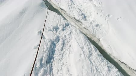 Mountaineer Steps Over Crevasse on the Glacier. FPV View Vídeos