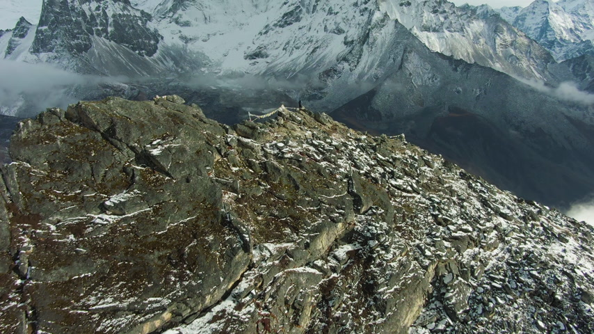 Hiker Man on Top of Nangartsang Mountain and Ama Dablam Mountain. Himalaya, Nepal. Aerial View. Drone Flies Forward, Tilt Up. Reveal Shot