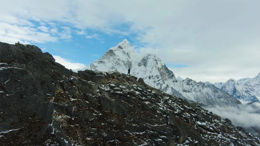Hiker Man Looking on Ama Dablam Mountain. Himalaya, Nepal. Aerial View. Drone Flies Forward and Upwards