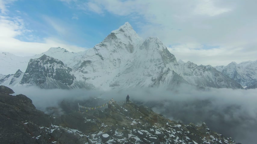 Man on Top of Nangartsang Looking on Ama Dablam Mountain. Himalaya, Nepal. Aerial View. Drone Flies Forward