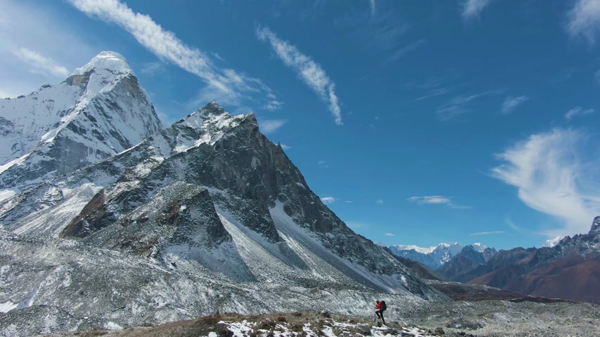 Ama Dablam Mountain and Man with Hiking Poles on Sunny Day. Blue Sky. Himalaya, Nepal. Aerial View. Drone Flies Sideways