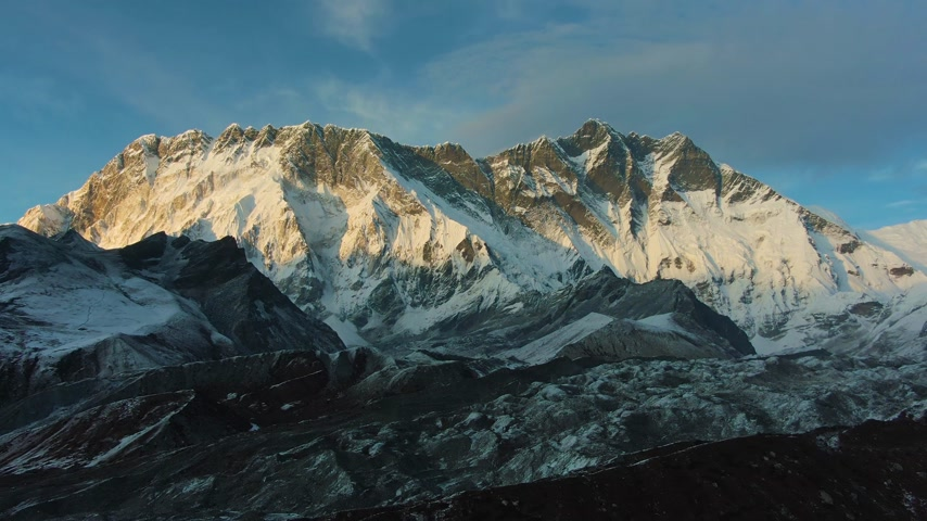 Nuptse Mountain and Lhotse South Face at Sunset. Himalaya, Nepal. Aerial View. Drone Flies Backwards
