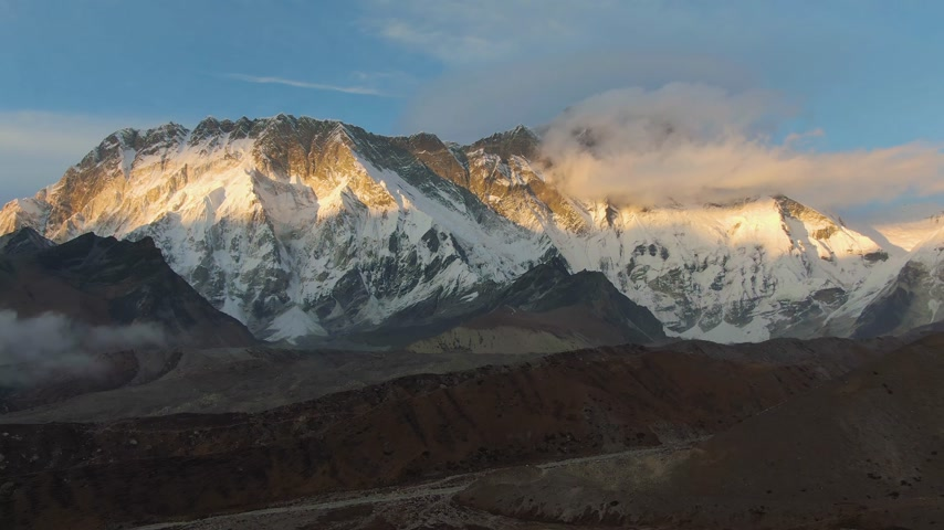 Nuptse Mountain, Lhotse South Face and Hiker Man at Sunset. Himalaya, Nepal. Aerial View. Drone Flies Backwards