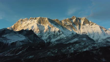 Mount Nuptse and Lhotse South Face at Pink Sunset. Himalaya, Nepal. Aerial View. Drone Flies Sideways and Upwards
