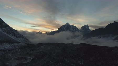 Taboche and Cholatse Mountain at Colorful Sunset. Himalaya, Nepal. Aerial View. Drone Flies Backwards