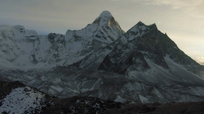 Ama Dablam Mountain at Sunset. Himalaya, Nepal. Aerial View. Drone Flies Sideways