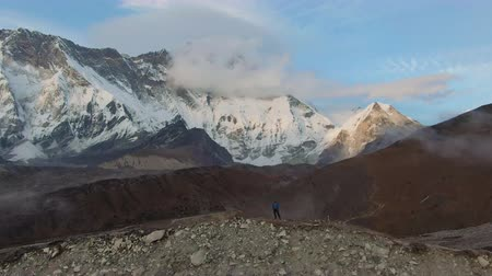 Lhotse South Face and Island Peak Mountain and Hiker Man at Sunset. Himalaya, Nepal. Aerial View. Drone is Orbiting