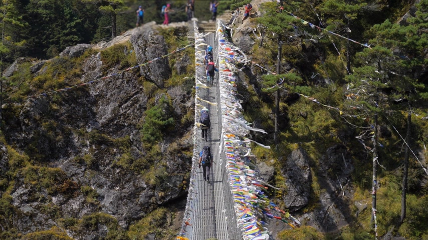 Trekkers are Walking on Suspension Bridge in Khumbu. Himalaya, Nepal. Slow Motion