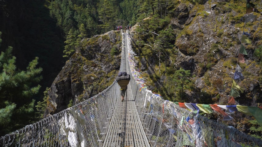 himalája : Porter is Walking on Suspension Bridge in Khumbu. Himalaya, Nepal. Slow Motion Stock mozgókép
