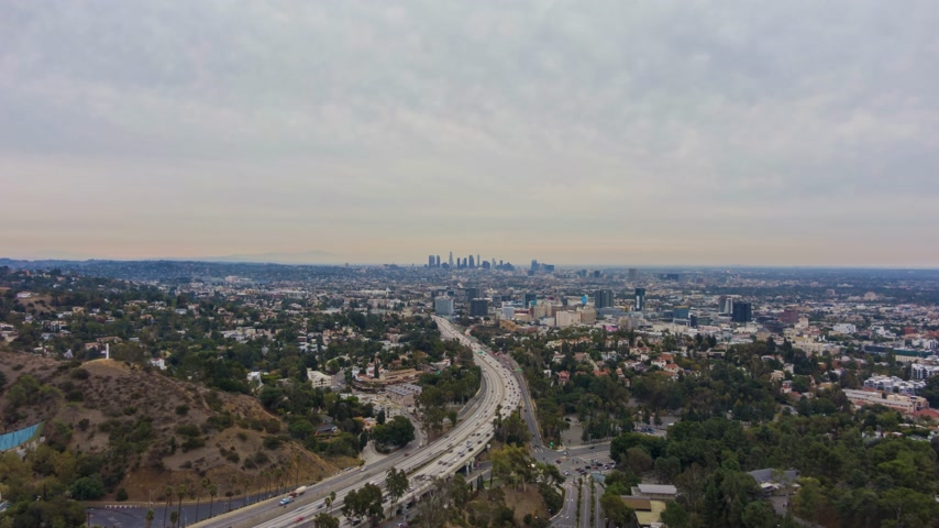 los angeles skyline : Los Angeles City in the Morning. California, USA. Aerial Hyperlapse. View From Hollywood Hills. Highway with Cars Traffic. Drone Flies Forward and Upwards Stock Footage