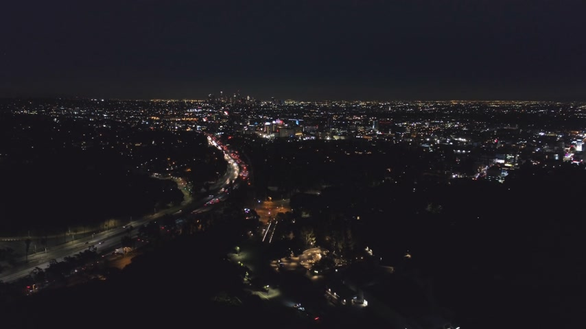 légi felvétel : Los Angeles City at Night. California, USA. Aerial View. View From Hollywood Hills. Drone Flies Sideways, Tilt Up