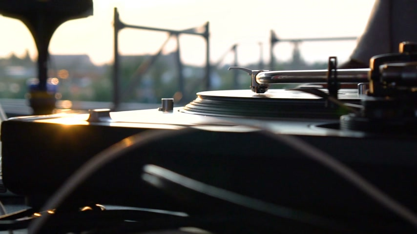 kalça : Mix and scratch, hands of a DJ on vinyl and mixer knobs. Slow motion 120 fps. Shooting with gimbal. Sunset. Stok Video