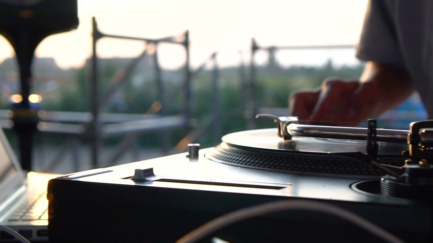 царапина : Mix and scratch, hands of a DJ on vinyl and mixer knobs. Slow motion 120 fps. Shooting with gimbal. Sunset. Стоковые видеозаписи