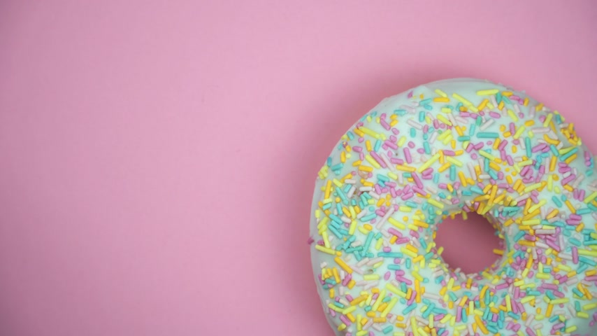 borrifar : Delicious sweet donut rotating on a plate. Top view. Bright and colorful sprinkled donut close-up macro shot spinning on a pink background. Stock Footage