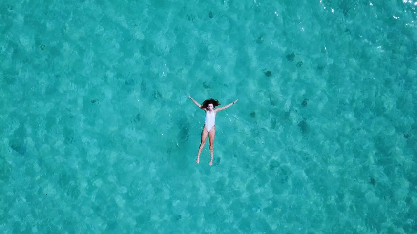 тропический : Aerial view. Beautiful young woman in white bikini floating on water surface in crystal clear turquoise color ocean Стоковые видеозаписи