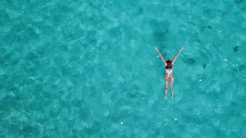 diretamente : Aerial view. Beautiful young woman in white bikini floating on water surface in crystal clear turquoise color ocean Stock Footage