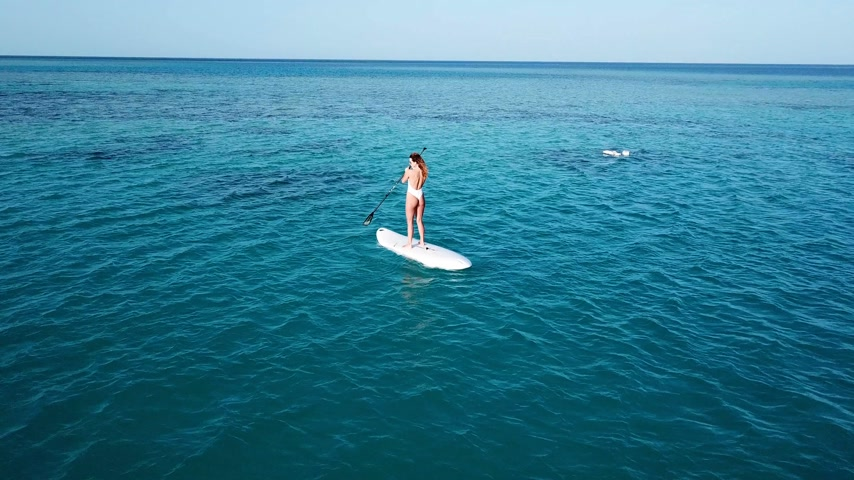 tyrkysový : Aerial view of young girl stand up paddling on vacation. Tracking shot of a young woman SUP boarding Dostupné videozáznamy