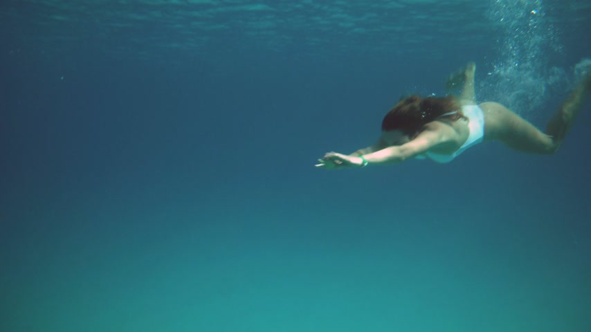 kobiety : Woman in blue bathing suit swimming underwater in slow motion