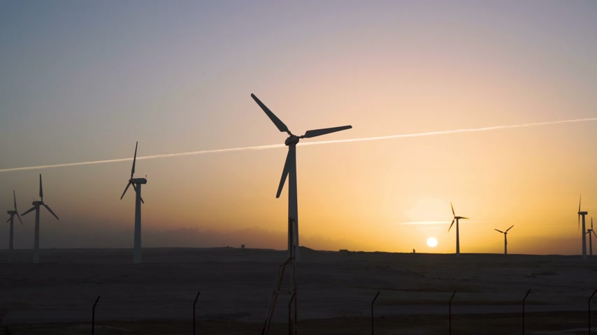 zmiany : 4K Beautiful windmill turbines harnessing clean, green, wind energy silhouetted in the sunset sky with sun rays. Green energy.