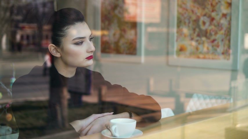 imitação : Melancholy time. Young miserable looking woman sits on windowsill and slowly drinks coffee. Stock Footage