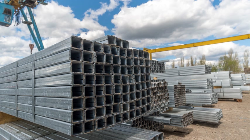 kütük : Metallic, steel or aluminum rectangular pipes and tubes on warehouse. Time lapse. Moving clouds Stok Video