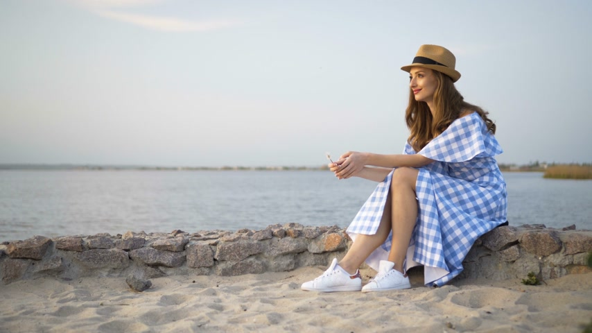 Санторини : Attractive woman in hat and dress is sitting and looking at sunset Стоковые видеозаписи