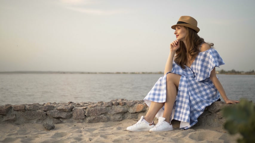 hostující : Attractive woman in hat and dress is sitting and looking at sunset Dostupné videozáznamy