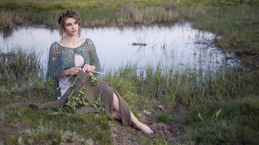 enchanted princess : Fairy tale. The charming girl sitting in the fairy lakeshore. Knitting