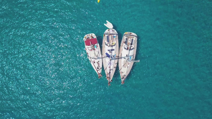 żaglówka : Top view of the sailing boats in blue lagoon. Swimmers enjoying in clear blue sea.