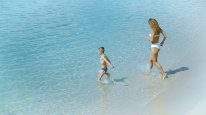 yürümeye başlayan çocuk : Mother playing with her little son and running in the sea at tropical beach