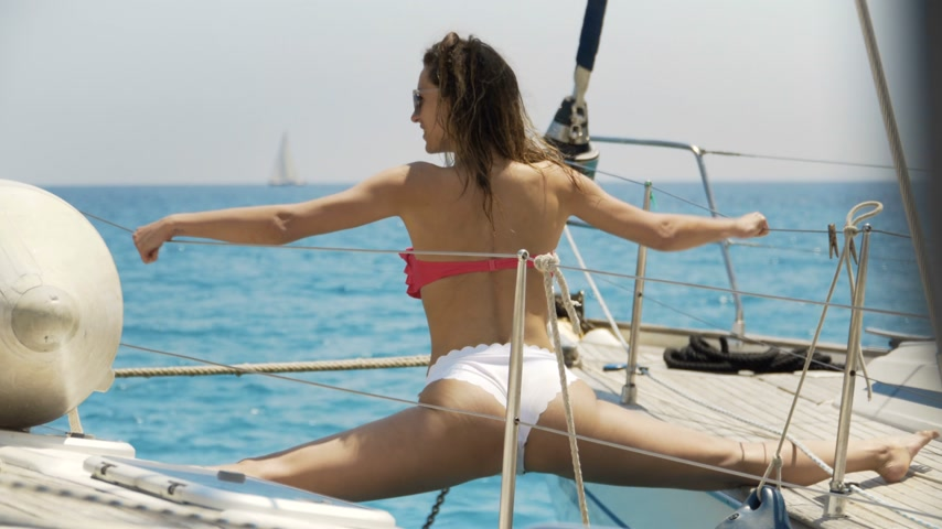 övgü : Close-up Shot of a Fit Young Woman Doing Yoga on a Sailing Yacht. In the Background Beautiful Calm Sea and Clear Sunny Sky