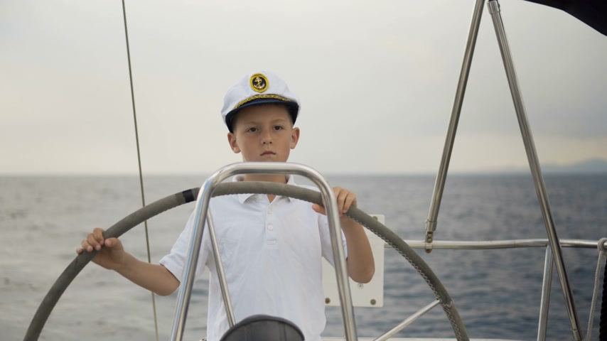 komutan : Litle children skipper at the helm controls of a sailing yacht during race. Stok Video