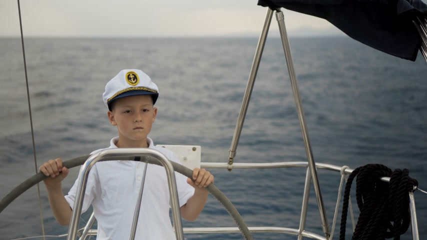 командир : Litle children skipper at the helm controls of a sailing yacht during race. Стоковые видеозаписи