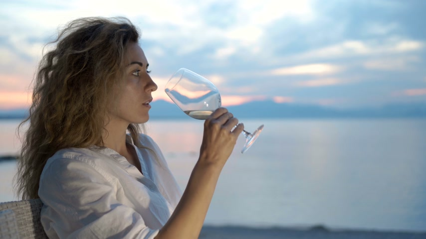 джакузи : Woman sipping white wine and enjoying the view of a beautiful golden summertime sunset.