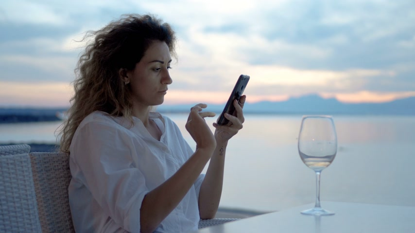 kifejező pozitivitás : A young woman takes a picture of a sunset and a glass of wine on the phone on the ocean coast