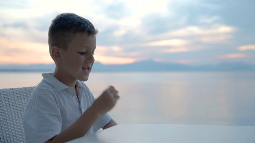 sáně : Close up view child boy hand holding and eating biscuits on the beach Dostupné videozáznamy