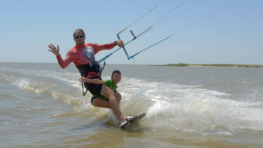 backflip : Slow motion. Dad and his son ride on kitesurfing together