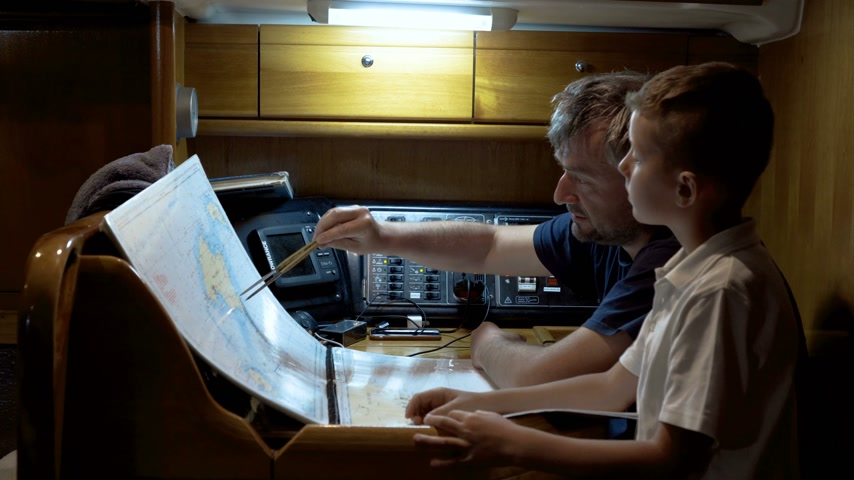 bússola : Father and son looking at map on the sailboat